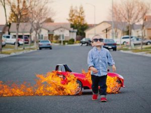 Small child in glasses walking away from a burning child-sized car