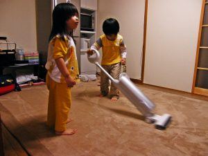 Two kids in the picture. One is holding a vacuum cleaner while the other kid watches on. Lazy kid.