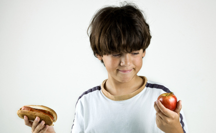 A young male kid holding an apple in his left hand, and a hot dog in the right. He looks indecisive as he is trying to figure out which is better.