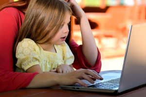 Kid looks at a laptop, enthralled by what's within. She's probably discovering the joy of budgeting. This is financial literacy for kids right here.